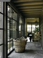 """A light-filled hallway, designed to resemble an enclosed porch, leads from the kitchen to the garage. """"I purposefully lowered the ceiling in that hallway to give it that cozy feeling,"""" says Dixon."""