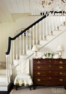 Cool white mixed with warm wood tones create a clean elegance beneath the stairwell.