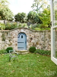 A custom undulating fieldstone wall and cheerful blue door transform the lawn into a secret garden, which was designed by landscape architect Richard Anderson.