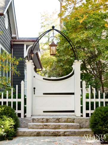 Architect Norman Askins emphasizes the cottage's storybook appeal with a custom gate and lantern.