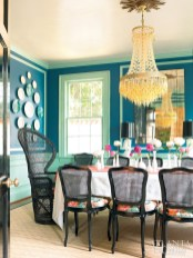 "Behind black lacquer doors, the dining room""s bold color palette is the perfect foil for the Murano glass chandelier. The dining room chairs are upholstered in Schumacher""s Chiang Mai Dragon fabric. The table runner belonged to Cinda""s grandmother."
