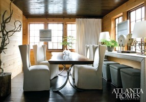 The dining room is a balancing act of materials, scale and shapes. Wing chairs dressed in linen slipcovers flank the slab-cut table, which is supported by curvy metal legs. Tangled driftwood branches add sculptural interest.