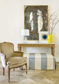 The designer's skill at mixing old and new is beautifully showcased in the foyer. A brass-framed antiqued mirror adds patina to the space, as do the antique console and antique bergere from Jane Marsden Antiques & Interiors, the latter still wearing its original fabric. An ottoman upholstered in an Old World Weavers striped print is tucked under the console for additional seating. The artwork is by Don Cooper, who is represented by Sandler Hudson Gallery.
