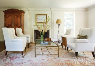 A large Oushak rug anchors the formal living room, part of the home's original footprint. Connor kept the color palette neutral and the windows bare, so as not to compete with the intricate architectural details. Cocktail table, Parc Monceau.