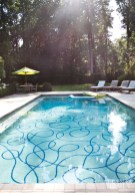 """A pair of tennis courts was removed from the property to make room for a pool and poolhouse. Jill Biskin, the artist commissioned to restore the Menaboni painting inside, was also responsible for creating the swimming pool design, inspired by a David Hockney painting. """"It's extremely modern and not at all what you would expect would go on the property,"""" says the homeowner of the hand-laid tile """"scribble,"""" but they couldn't be more pleased with the result."""