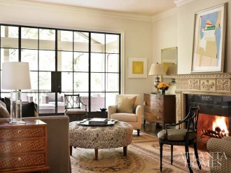 An antique Aubusson rug anchors the living room. The homeowners rotate their collection so that works of art are never touched by direct sunlight. A piece by Robert Motherwell is propped above the mantel. A yellow abstract by Josef Albers nestles in the corner.