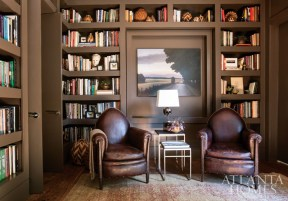The library is dark, cozy and handsome and filled with the homeowners' personal treasures, including baskets from their travels to Botswana. A paneled wall with a painting by Georgia artist Bill Turner opens to reveal a Murphy bed. Skull lamp by Blackman Cruz, available through R Hughes. The Turkish rug is from Sullivan Fine Rugs. Nesting tables and antique leather chairs with nailhead trim, Nicholson Gallery.