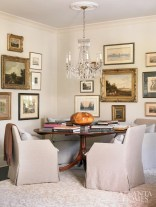 """Tucked into a corner of the living room is a gathering spot designer Carter Kay likens to a """"French salon."""" The cozy nook serves as the showcase for the family's art collection. Anchored by a dining table from the couple's former home, it is surrounded by comfortable John Saladino swivel chairs."""