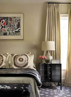 The master bedroom is an intimate space that is soft and inviting. The bedding from Restoration Hardware complements the rug and chairs from ABC Carpet and Home. A piece by Joan Miro hangs over the bed. End table, Bungalow Classic. Lamp, Mitchell Gold + Bob Williams.