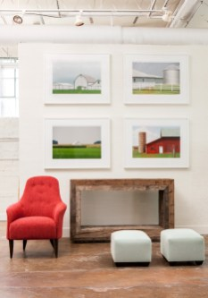 Fine art photography by Kathleen Walker hangs above a console by Skylar Morgan Furniture + Design. The chair and ottomans are by Bjork Studio.