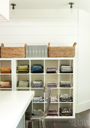 Fabric samples are organized by color in modular bookcases.