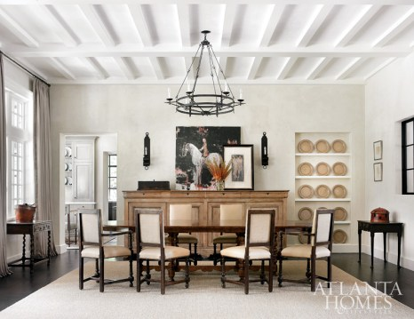 The dining room in this Tuxedo Park home designed by architect Peter Block and interior designer Joel Kelly possesses medieval flair. The trestle table is by Formations at Jerry Pair; Parsons chairs from 14th Street Antiques; sideboard from Provenance Antiques; oil painting from Tew Galleries; sconces are from Ainsworth-Noah; and iron chandelier from Dessin Fournir.