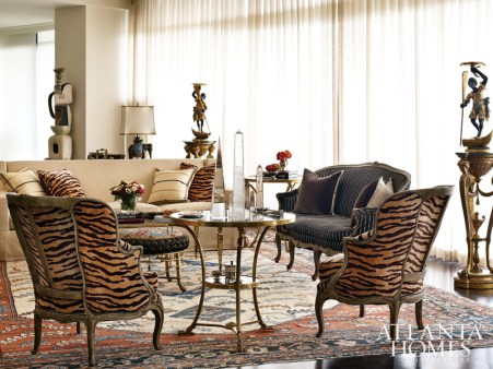 The living room is a study in sophisticated eclecticism, where neutral walls balance out a mix of patterns and gilt touches. The Verona sofa by Ebanista is covered in Villis Strie-Pearl from Schumacher with pillows by Travis and Company and Max and Company. A pair of painted French bergere chairs upholstered in an animal print date back to 1860.