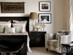 A neutral palette creates a calming effect in the guest suite. Summer Hill La Donna bedding from Ainsworth-Noah is punched up with a Madison chair from Baker Knapp & Tubbs in striped fabric. A carved Dogon door from Mali hangs over the bed.
