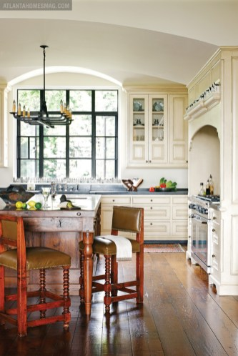 A masterfully designed kitchen by Connecticut-based Crane Woodworking combines the best of old and new: barstools from Holland & Co. and an antique chandelier found at Ma Maison.