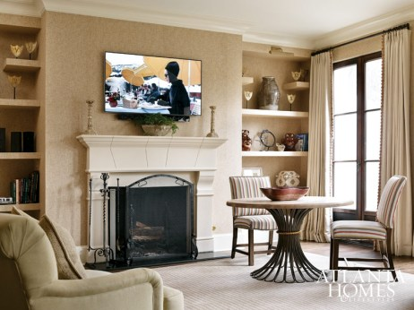 Formality is dialed down in the media room, anchored by a round dining/game table from BeeLine Home. Open shelving niches flanking the fireplace are unified with textured wallpaper.
