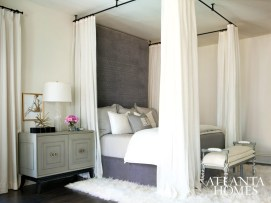 A Mongolian lamb rug grounds the draped bed, with a headboard covered in a custom fretwork velvet from Lewis & Sheron.