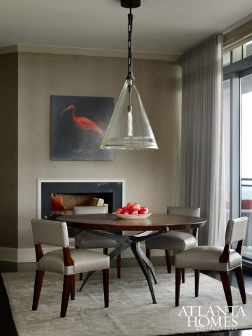 A conical Mattaliano chandelier floats above a custom wood and iron table in the dining room, while a painting by Todd Murphy adds a dash of color to the space.