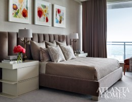 A custom headboard and side tables by Bjork Studio create clean, modern lines in the bedroom, where a triptych by Allison Stewart adds color. Bedside lamps from Gramercy Fine Linens. Shades from Lamp Arts.
