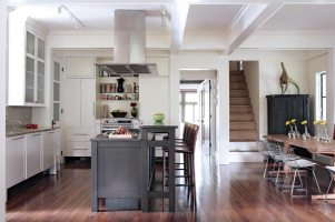 In the main living space, rooms are defined by the beams overhead, demarcating the bounds of the hallway between the kitchen and dining areas, left. Even within the kitchen, a deft use of materials designates different zones. The dark-stained island is the food prep area, while limestone-topped cabinetry along the back wall is delegated to clean up. Hood and cooktops, Gaggenau. Refrigerator, Sub-Zero. Sinks, Franke. Island countertops and backsplash, Walker Zanger, (404) 365-9991. Cabinetry, Phil Plunket Custom Cabinetry, (770) 945-4566.