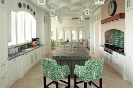 In the kitchen, Roberts played off his love of green by mounting an oversized antique clock and oyster plates above a pair of niches outfitted with green-and-white tile backsplashes. Two pairs of slipcovered bar stools flank the diamond-green granite countertops.