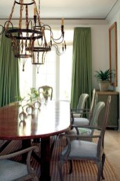 """Roberts enlisted Edgar-Reeves to hand-bead a pair of chandeliers for the dining room. The table is large enough to seat three generations of the client""""s family and makes for a fresh contrast against the whitewashed floors."""