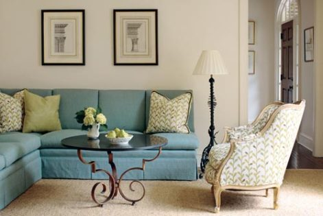 """A wall-hugging banquette in one corner of the living room provides an abundance of seating in a minimal space. The accompanying French chair gets a fresh point of view, too, with a small-scale print that bears out the room""""s predominant hues."""