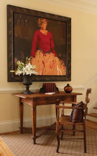 A striking oil painting by Craig Alan hangs above a warm-toned antique desk, greeting visitors as they sweep through the house and ascend the stairway.