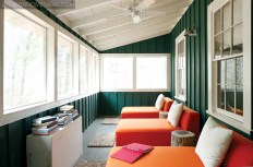 This lake-facing sleeping porch dons chic orange chaises from CB2.