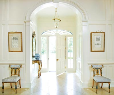 """The pair of gilded chairs in the home""""s entryway came from the Gianni Versace mansion in Miami Beach, Florida, following Versace""""s passing in 1997. Kasler purchased them from William Word Antiques, and loved them so much that she made no alterations""""even the blue silk damask fabric is original."""
