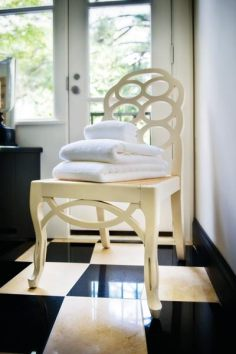 """The iconic Loop chair""""a Frances Elkins design""""puts a stack of towels within easy reach. Towels, Belle Chambre."""