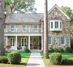 A facade of Cashiers, North Carolina, fieldstone and a luxuriously large front porch, where the homeowners Bonneau and Jennifer Ansley can often be found, ensure that this newly constructed Dutch Colonial home complements its mature neighborhood. Wicker, Mainly Baskets. Lanterns, Bevolo.