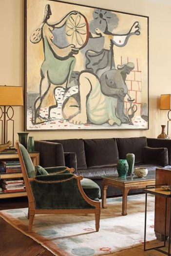 """In the living room, standout pieces include the massive Stephanus Heidacker painting, Lager der Amazonen, above the sofa, as well as the 1920s Chinese Deco rug, which Katie discovered at her mother""""s house in Bermuda. Katie acquired the coffee table, by noted artist Max Kuehne, from dealer Deanne Levison."""