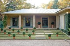 """The home""""s fa�?§ade is covered in smooth coat stucco. The lines of the copper roof are perpendicular to the concrete garden borders below. Italian terra cotta pots are planted with American boxwood."""