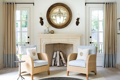 """The palest of blues combines with neutral hues in this pool house, adding to the relaxing atmosphere created by Gretchen Edwards and Mary Allison Buzzell. Adding to the sense of calm is the symmetry of the room, exemplified by this pair of chairs in front of the limestone fireplace. """"This was one of my most rewarding projects,"""" says Edwards. """"The client was so open-minded and [the pool house] had wonderful bones thanks to Yong Pak."""""""