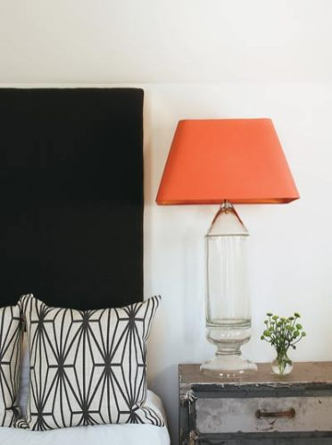 A gray wool headboard had to be completed in the master bedroom, because the finished product wouldn't make it upstairs. The glass lamp set atop a custom metal cabinet has made it through three of Douglass' moves, a badge of honor for any piece. Lamp, Ainsworth-Noah.