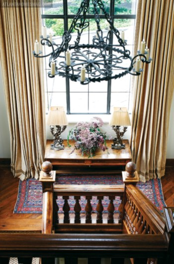 On the stairway landing, a Paul Ferrante chandelier is the perfect complement to stalwart steel window frames by Crittall. Lamps by Linda Horsley Antiques. Tables from Robuck & Co. Curtain fabric, Rose Cumming.