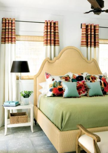 """Because windows and doors crowded the spaces where a bed would have typically been placed, the design for the master bedroom began as a challenge. But Musso soon realized that the multiple windows were a blessing in disguise. After setting the bed between two of them, he took cues from the sun-drenched space and reflected it in colorful fabrics""""a hand-painted Rubelli floral and a Liberty stripe."""