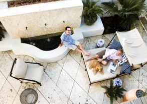 """Global influences have greatly informed the designs of Bill Musso (left), who enjoys mixing high and low. Case in point: An inexpensive, streamlined lounger and chairs from Restoration Hardware, corralled in the courtyard, provide shade on hot summer days and give the couple""""s cocker spaniel, Aaron, a regal spot for repose. The harlequin pattern of the Dominican shellstone was original to the house."""