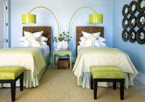 """In this guest bedroom, cheery Bauhaus-style arc lamps and a wall of playful convex mirrors make it a favorite haunt for children. Still, """"the room is not so juvenile that adults can""""t stay here,"""" adds Musso. The designer chose fresh shades of green to complement the watery hue of the walls, as captured beautifully in the Victoria Hagan fabric he used for the shams and window treatments."""