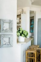 A kitchen pass-through provides a place to grab a snack or quick meal. Even nearby artwork takes a laid-back approach; a pair of old frames from 14th Street Antiques displays rocks collected by the owners.