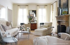 """Soft neutral hues give the living room a comfortable and relaxed feeling. Even the art over the fireplace """"keeps it romantic,"""" says Howard. """"It sort of brings the room down a notch, makes it more casual."""" Further enhancing the laidback look is a heavily antiqued mirror, which the designer was lucky enough to find at an antiques market."""