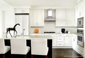WHITE AND BRIGHT Opposite the dark and dramatic dining room, the kitchen—decked out in white, right down to the Charles Stewart barstools seems even brighter in comparison. It's the perfect backdrop, too, for the perfect accessory, a charcoal-color sculptural horse.­