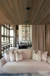 A pair of curvy, back-to-back Holly Hunt sofas holds court in the combination living/dining room of the Giles residence. The wooden ceilings are formed from 100-year-old Canadian cedar. A sumptuous, multi-zone interior gets its cozy aura from tufted upholstered wall panels and double-height draperies.