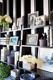 """Open shelving from Hayneedle keeps a collection of books and accessories from Wisteria within arm""""s reach in Liz Killmond""""s menswear-inspired office."""