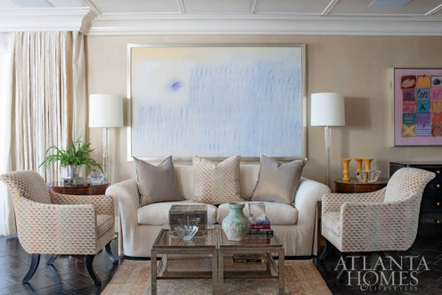In the living room, designed by Stan Topol, a painting by artist Alice Andrews hangs above a J. Robert Scott sofa. The other painting, at right, is by Ida Kohlmeyer. Regency Sabreleg armchairs by Rose Tarlow Melrose House flank a pair of vintage cocktail tables from Maison Gerard in New York that are credited to Willy Rizzo. The three yellow Peking glass vases are from JF Chen in Los Angeles. Lamps, J. Robert Scott. An antique Khotan rug from Moattar, Ltd., anchors the space.