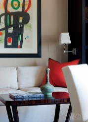 A sitting area in the husband's office includes a Miro lithograph. The William Switzer coffee table is macassar ebony with bronze hardware, and the Lucien Rollins wall lamp is polished nickel—both are available through Ernest Gaspard & Associates. The pillow fabric is by Bergamo, available through Donghia.
