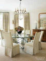 A Niermann Weeks chandelier hangs above the round dining room table. Linen velvet-covered chairs add a luxurious sheen to the graceful space.