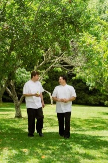 """Chefs Johannes Klapdohr and Chris Huerta stroll through the bountiful orchard""""part of the 33-acre setting at The Farm."""
