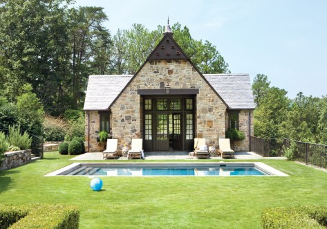 """For the outdoor living spaces of this English-style pool pavilion designed by the architectural firm Henry Sprott Long and""""Associates, decorator Phoebe Howard chose elegant Kingsley-Bate chaise longues and ceramic garden seats. """"I love mixing teak and porcelain,"""" says Howard. """"It brings an """"indoor"""" look outside."""" Landscape design by Kelly Hulsey."""